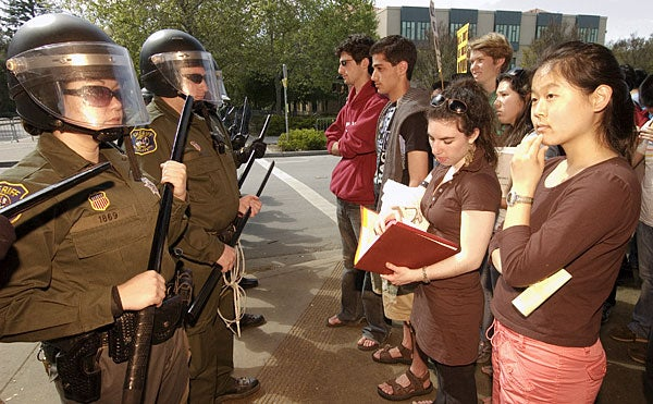 photo of Stanford students staring at police at a               protest of a visit by President George W. Bush in 2006