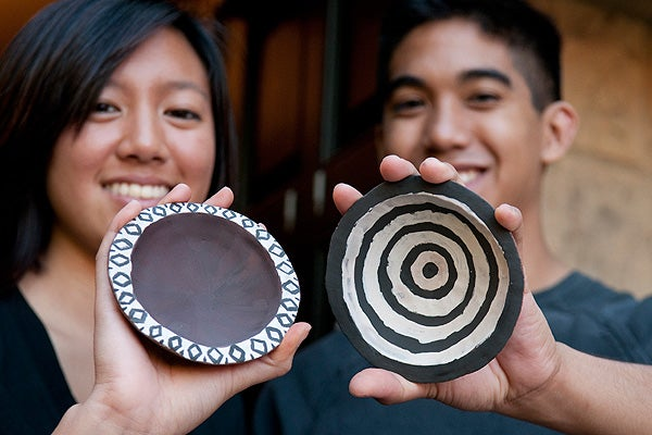 Freshmen Bettina Tiangco and Joshua Coronado show their bowls before firing.