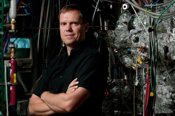 Nick Melosh, assistant professor of materials science and engineering, stands beside the ultra-high vacuum chamber used in the tests that proved the PETE process works.