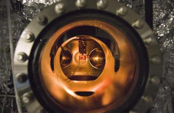 A small PETE device made with cesium-coated gallium nitride glows while being tested inside an ultra-high vacuum chamber. The tests proved that the process simultaneously converted light and heat energy into electrical current.