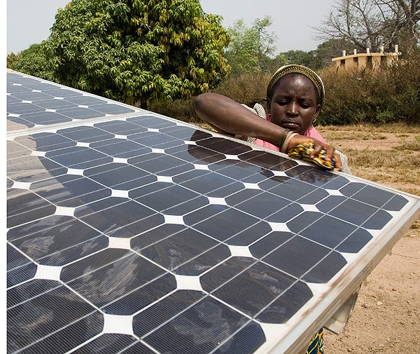 A woman cleans a solar panel that powers the drip irrigation system in a rural village in Benin.