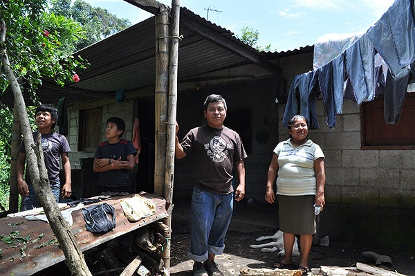 Leonzo Upun and Adelaida Soco Gonzales with two of their four sons. The family moved to San Juan El Mirador thanks to a land redistribution program allowing them to own a house and some property.