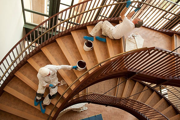 Painters put the finishing touches on the banister of the grand staircase in the Gunn Building on Tuesday afternoon.