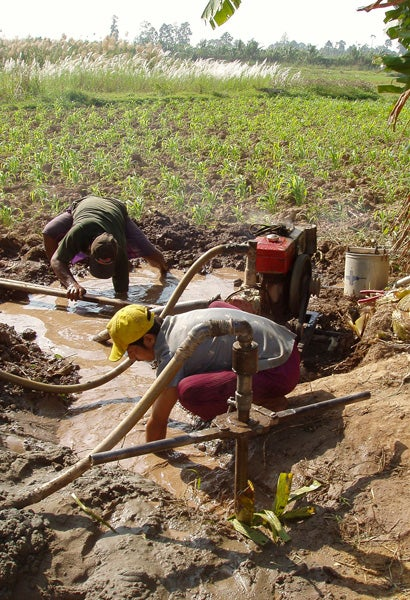Two Cambodian men drill into a shallow aquifer to collect drinking water.