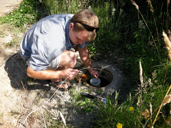 Graduate student Nick de Sieyes deploys a data logger into a monitoring well at Stinson Beach.