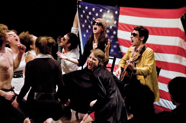 Performers shouting in front of an American flag