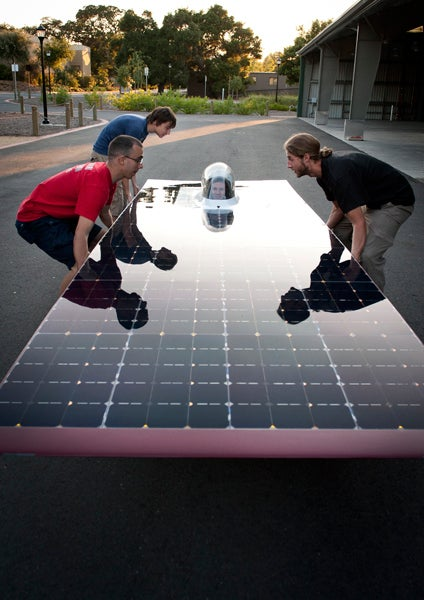 Members of the team prepare to lift the solar car