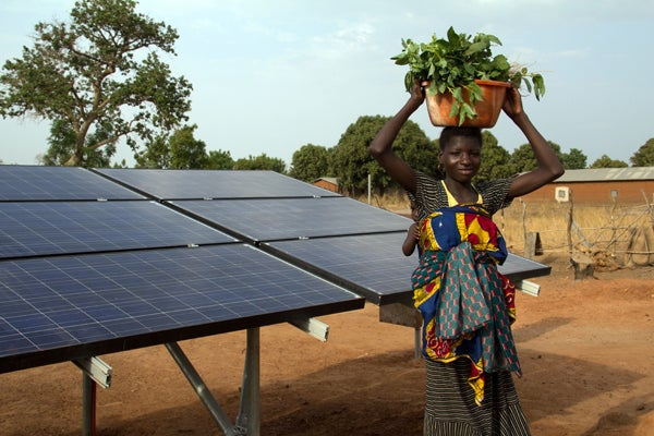 Woman next to solar panels that are powering a solar drip irrigation system for collective women's garden in Kalale, Benin.