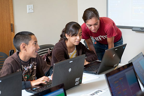 Devney Hamilton helping students at computers