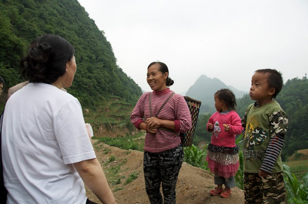 Linxiu Zhang, REAP's co-director, left, talks with Li Qunyan, center, who lives in a rural village of about 2,000 people in Guizhou Province.