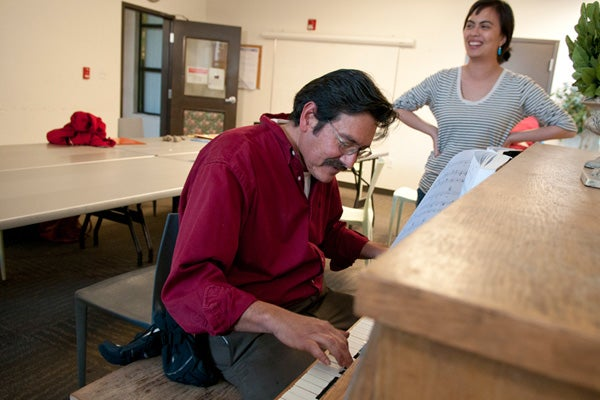 Client plays piano as student volunteer stands nearby