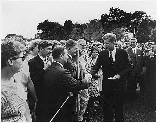 President John Kennedy shaking hands with a crowd