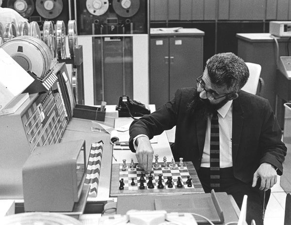 John McCarthy playing chess in front of a large computer