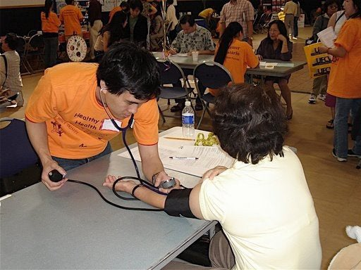 Young man checking the blood pressure of a woman at a screening