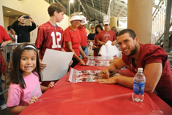 Child getting autograph from Andrew Luck