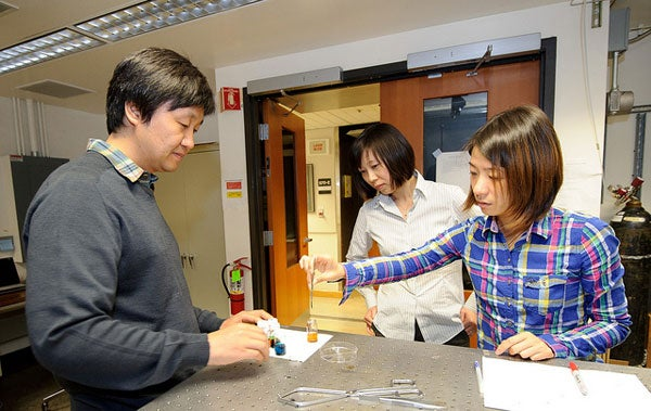 Assistant Professor Xiaolin Zheng,center,  watches as post-doctoral fellow In Sun Cho, left, and PhD student Yunzhe Feng, right, prepare nanowires with a solvent-based gel of metal and salt.