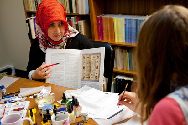Stanford scholar Ozgen Felek shows an example of an illuminated manuscript in a class