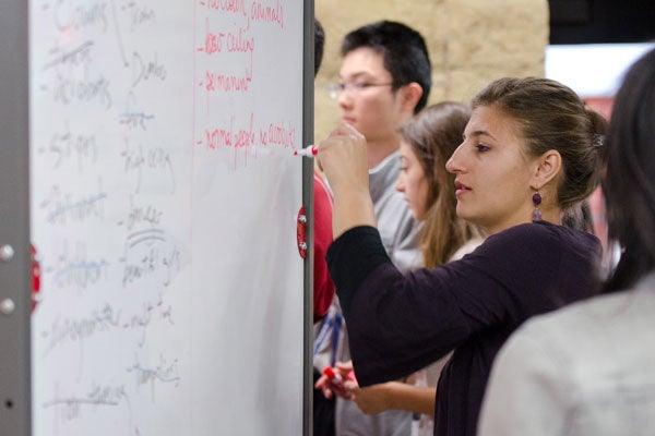 Graduate student Victoire Lejzerzon takes notes on the whiteboard during an exercise.