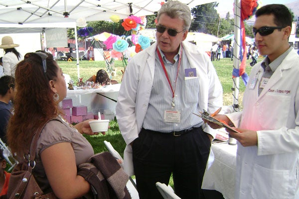 Gabriel Garcia talking with woman at cultural celebration