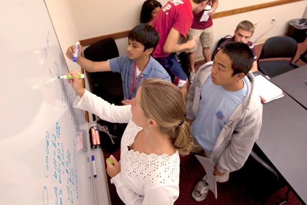 Students at white board with teacher