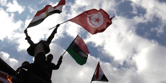 Protesters wave Egyptian, Libyan, and Tunisian flags during a protest in Tahrir Square on April 8, 2011.