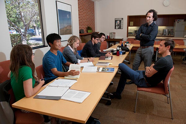 High school students at a table with with Stanford Professor Dan Edelstein (standing) and resident counselor Nathan Lindborg at the Summer Humanities Institute.