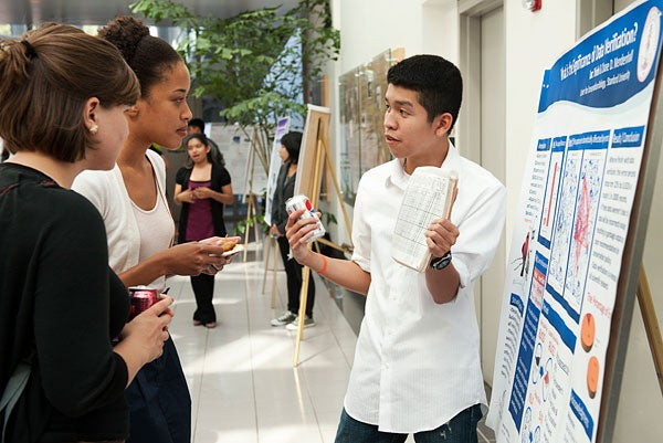 Loc Trinh, right, a junior at Silver Creek High School in San Jose, Calif., explains his poster to Stanford graduate students Molly Lewis, left, and Melinda Belisles.
