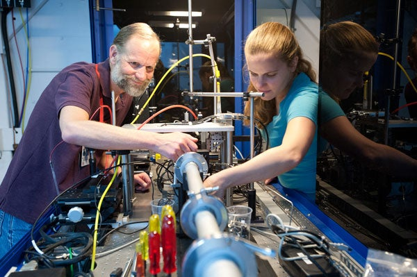Senior staff scientist Mike Toney and postdoc Johanna Nelson inspect the transmission X-ray microscope at SLAC's Stanford Synchrotron Radiation Lightsource, a powerful device that takes nano-scale images of chemical reactions in batteries while they are r