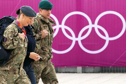 Members of the armed forces walk past the Olympic rings on the perimeter of the Olympic Park in Stratford, the location of the London 2012 Olympic Games, in east London on July 15, 2012.