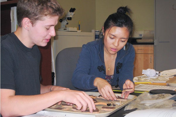 Students Kyle Lee-Crossett and Stephanie Chan working with the collection