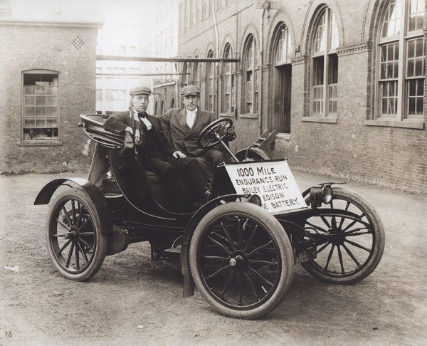 Historic photo of two men in a battery-powered car in 1910.
