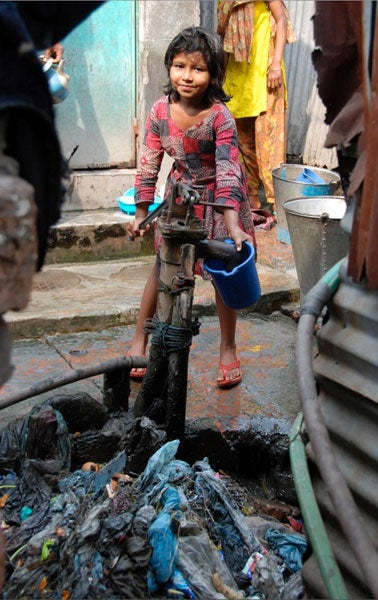 Girl pumping drinking water in Dhaka, Bangladesh.