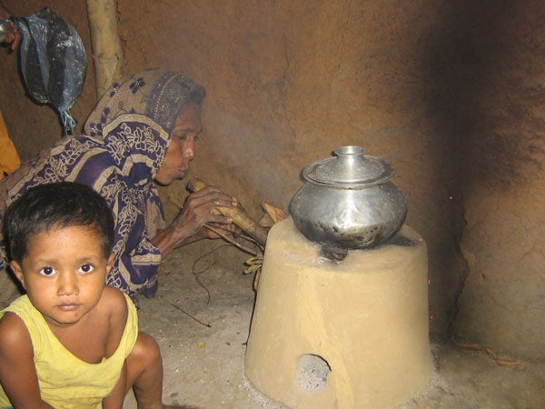 A Bangladeshi woman stokes a flame under a traditional stove.