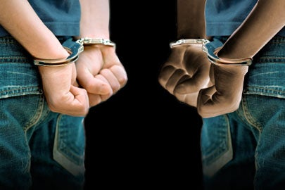 Illustration showing white and black hands in cuffs