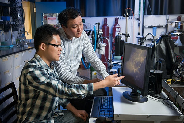 Graduate student Guosong Hong, left, and chemistry Professor Hongjie Dai look at the vascular structures in a mouse model of peripheral arterial disease.