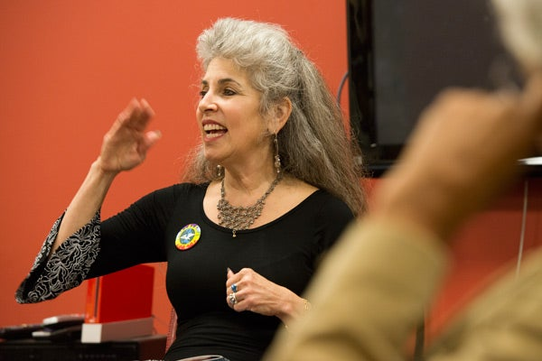 Juana Alicia speaks at an event that  introduced her murals to the campus.