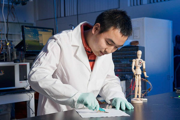Post doctoral scholar Chao Wang cuts through a sample of the self-healing plastic material developed in the Bao lab.