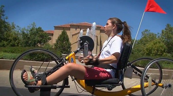 Student Molly Fausone riding a hand-operated bicycle on campus