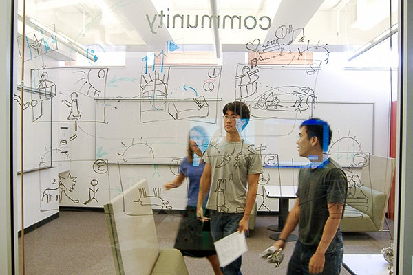 Students in front of line drawings on board.
