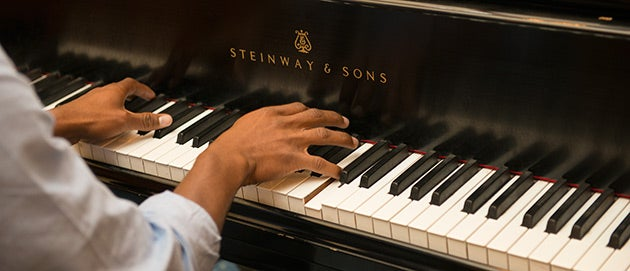 Closeup of someone playing a Steinway and Sons piano