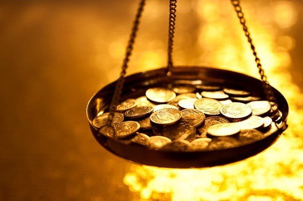 Image of a scale with coins surrounded by fire
