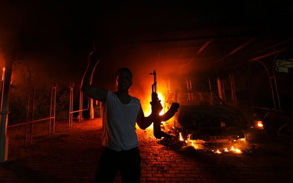 A protester reacts as the U.S. Consulate in Benghazi, Libya, is seen in flames.