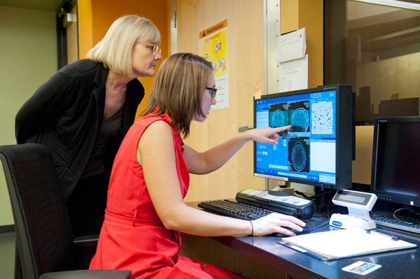 MRI facility manager Laima Baltusis, left, observes the scan with Natalie Phillips.