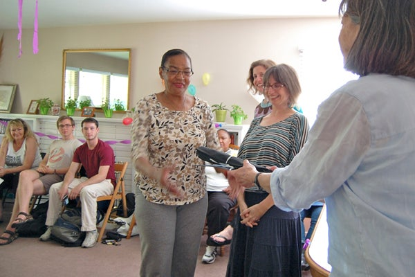 Wende C. receives her completion certificate from the Hope House Scholars program as Stanford student tutors look on.
