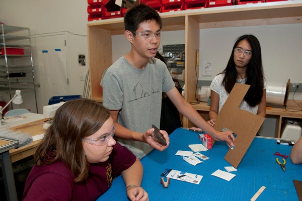 Flanked by 18-year-old Zoe Nuyens (left) and 17-year-old Justine Sun, Alex Lee, also 17, demonstrates a system for detecting surgical gauze