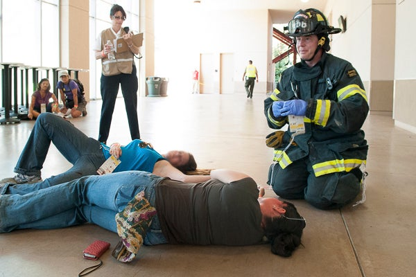 A firefighter helps two 'victims' of a mock explosion at the Stadium while an observer from Palo Alto Fire Department looks on.
