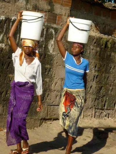 Two African women carrying water buckets on their heads