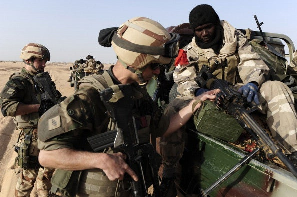 A French soldier looks at the weapon of a Malian soldier as they enter Bourem, northen Mali