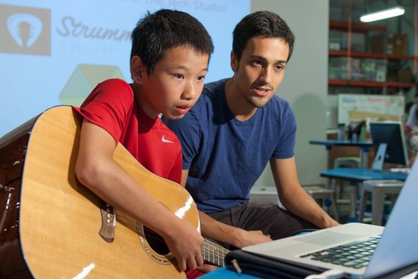 Jim Huang, 12, picks a string as he follows the instructions on the interactive web application called Strummify designed by graduate student Danny Cochran, right.
