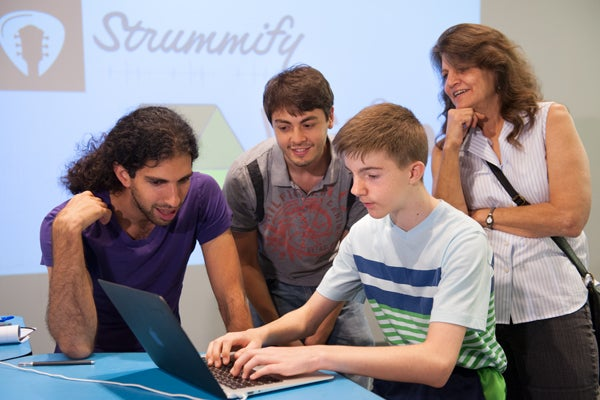 Graduate students Amit Deutsch, left, and Mohamed Yassine observe as Kevin Hodge, 13, of Sacramento, interacts with their application 'Worlds,' while Kevin's mom, Paula Badella, looks on.